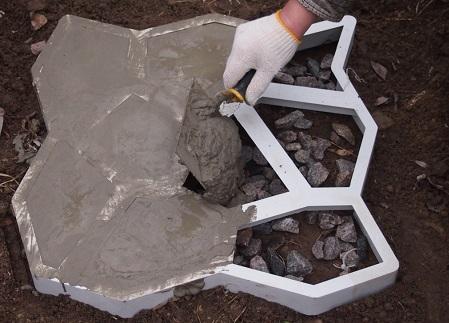 Укладка бетонного раствора в опалубку для садовой дорожки
