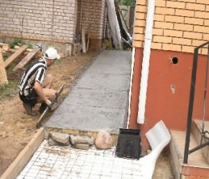 Процесс заливки отмостки вокруг дома